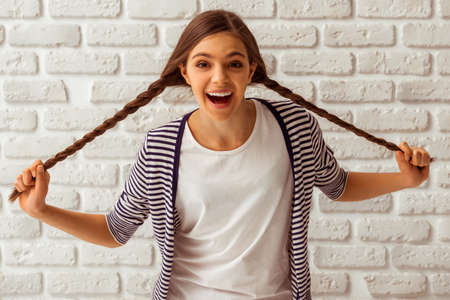Cute teenage girl in casual clothes playing with her braids, looking in camera and smiling, standing against white brick wall Stock Photo