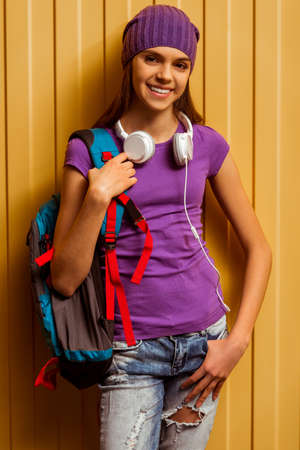 Cute teenage girl in a t-shirt and a cap standing with a school backpack and headphones on an orange background,  looking in camera and smiling