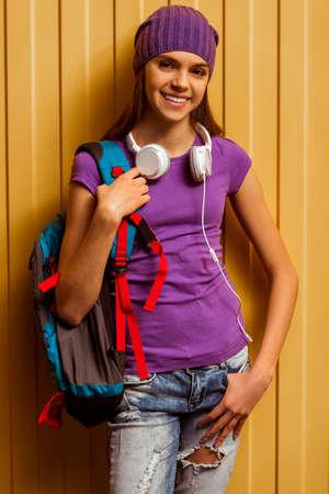 T シャツとキャップ学校のバックパックとオレンジ色の背景上のヘッドフォンの側に立って、カメラで見て、笑顔のかわいい十代の少女 写真素材