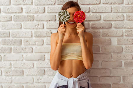 wall covering: Portrait of a cute teenage girl in a top and shorts covering her eyes with lollipops, looking in camera and smiling, standing against white brick wall Stock Photo