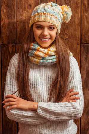 arma: Portrait of a cute teenage girl in a scarf and a cap looking in camera and smiling, standing on a wooden background