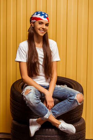 bandana girl: Cute teenage girl in a t-shirt, jeans and a bandana looking in camera and smiling while sitting on tires against orange background