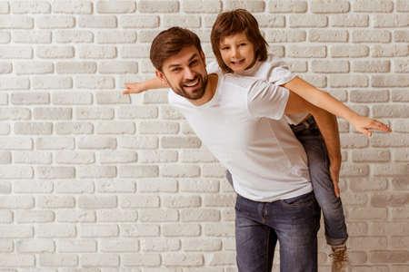 Portret van een knappe vader die zijn leuke zoon op de rug. Zowel in witte t-shirts glimlachen, staande tegen een witte bakstenen muur.