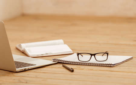 open floor plan: Laptop, eyeglasses and some office supplies on wooden surface