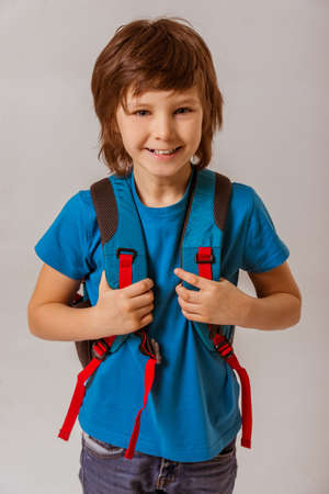 brown haired: Portrait of a cute little schoolboy in a blue t-shirt with a backpack looking in camera and smiling while standing on a gray background