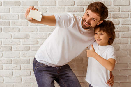 Handsome young father making a photo with his cute little son. A little boy showing OK sign. Both in white t-shirts smiling, standing against white brick wall.
