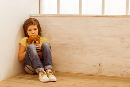 white bear: Punished little boy sitting in the corner and hugging a teddy bear