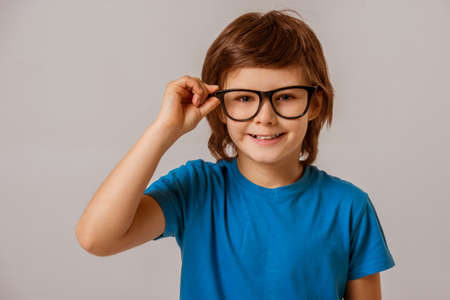 young boy smiling: Portrait of a cute little boy in a blue t-shirt  and eyeglasses looking in camera and smiling while standing on a gray background