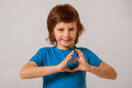 modern love: Portrait of a cute little boy in a blue t-shirt  showing a heart with his hands, looking in camera and smiling while standing on a gray background