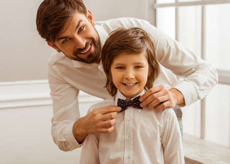 Handsome young father adjusting his cute little sons bow tie. Both white classical shirts looking in camera and smiling