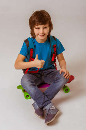 cute boys: Cute little schoolboy in a blue t-shirt with a backpack showing OK sign, looking in camera and smiling while sitting on a skateboard on a gray background