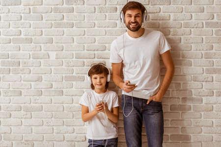 잘 생긴 젊은 아버지와 그의 귀여운 작은 아들은 음악을 듣고 카메라를보고 웃 고, 스마트 폰을 사용. 모두 흰색 티셔츠와 청바지, 흰색 벽돌 벽에 서.