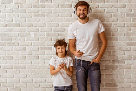 Handsome young father and his cute little son using smart phones, listening to music, looking in camera and smiling. Both in white t-shirts and jeans, standing against white brick wall.