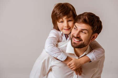 Retrato de un padre hermoso que lleva a su hijo lindo en la espalda y sonriendo. Tanto en blanco camisas clásicas de pie sobre un fondo gris.