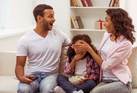 daugther: Cute little Afro-American girl and her beautiful young parents sitting on a sofa and watching TV. Man and woman looking at each other with surprise. Father holding a remote control, daughter eating popcorn, mother covering her daugther eyes.