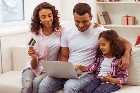 parent: Cute little Afro-American girl and her beautiful young parents using a laptop and doing shopping online while sitting on a sofa at home. Mother holding a credit card.