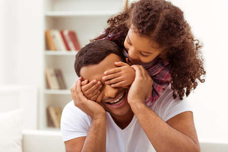 happy home: Cute little Afro-American girl in casual clothes covering her father eyes. Both smiling.