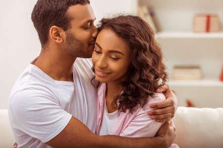 femme romantique: Jeune beau couple �treindre afro-am�ricaine et souriant alors qu'il �tait assis sur un canap� dans la chambre. Man embrasser sa femme.
