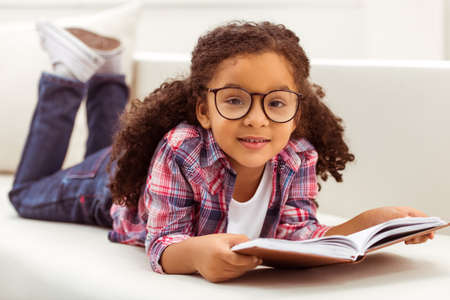 Cute little Afro-American girl in casual clothes and eyeglasses reading a book, looking at camera and smiling while lying on a sofa in the room.