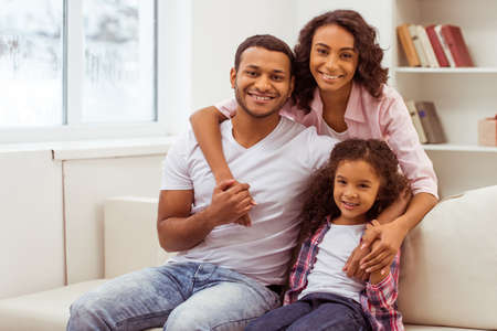 Cute little Afro-American girl and her beautiful young parents hugging, looking at camera and smiling while sitting on a sofa in the room. Foto de archivo