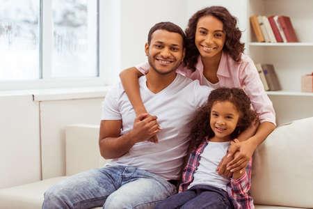 familia abrazo: niña afroamericana linda y sus bellos padres jóvenes abrazando, mirando la cámara y sonriendo mientras está sentado en un sofá en la sala. Foto de archivo