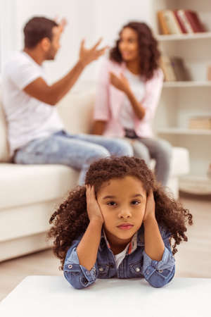 disobedient child: Cute little Afro-American girl covering her ears, in the background her parents quarreling. Stock Photo