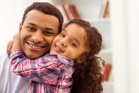 Portrait of a cute little Afro-American girl in casual clothes cuddling her handsome father. Both looking at camera and smiling. Stock fotó