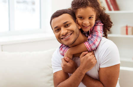 Cute little Afro-American girl in casual clothes cuddling her handsome father. Both looking at camera and smiling.