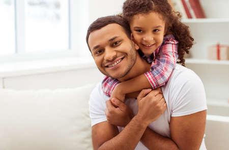 familia abrazo: niña afroamericana linda en ropa casual que abraza a su apuesto padre. Ambos mirando la cámara y sonriendo.