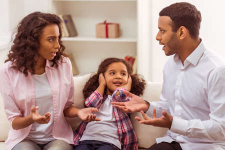 disobedient child: Cute little Afro-American girl covering her ears while her parents quarreling.