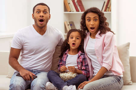 Cute little Afro-American girl and her beautiful young parents looking at camera and showing surprise while sitting on a sofa and watching TV. Father holding a remote control, daughter holding a bowl with popcorn. Banque d'images