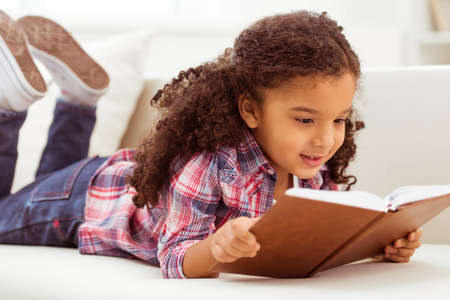 Cute little Afro-American girl in casual clothes reading a book and smiling while lying on a sofa in the room.