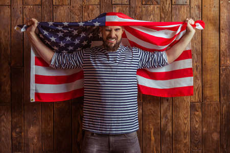 striped vest: Stylish man with beard in striped vest holding the American flag and showing emotions, standing on a wooden background Stock Photo