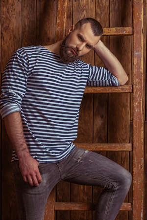 striped vest: Stylish man with beard in striped vest leaning on a ladder and looking at camera, standing on a wooden background