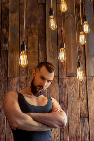 singlet: Attractive stylish man with beard in black singlet looking at camera, standing on a wooden background
