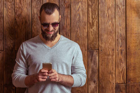 cool gadget: Stylish man with beard in gray sweater and sunglasses using a mobile phone and smiling, standing on a wooden background Stock Photo