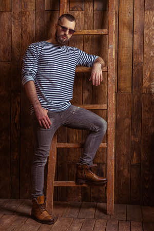 striped vest: Stylish man with beard in striped vest and sunglasses leaning on a ladder, looking at camera, standing on a wooden background