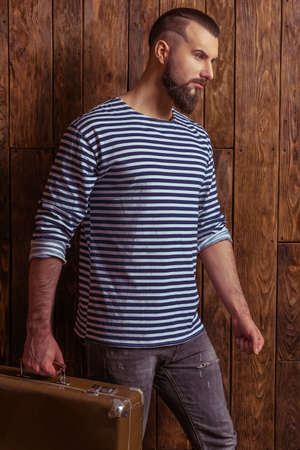 striped vest: Side view of stylish man with beard in striped vest holding a suitcase, standing on a wooden background