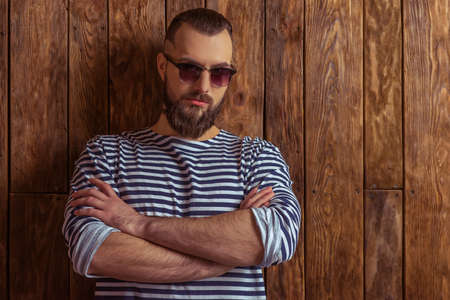 striped vest: Stylish man with beard in striped vest and sunglasses, looking at camera, standing on a wooden background Stock Photo