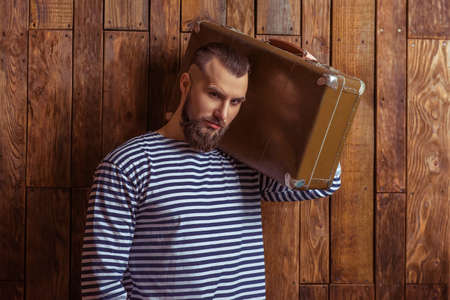 striped vest: Stylish man with beard in striped vest holding a suitcase and looking at camera, standing on a wooden background