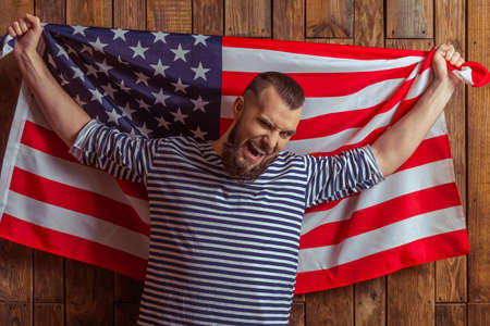 striped vest: Stylish man with beard in striped vest holding the American flag and screaming, standing on a wooden background