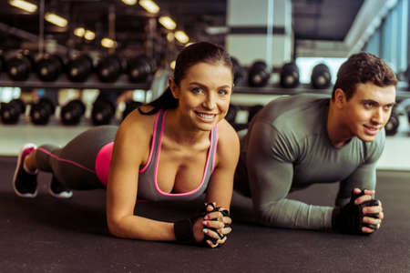 laying abs exercise: Attractive young muscular man and woman doing plank exercise and smiling while working out in gym
