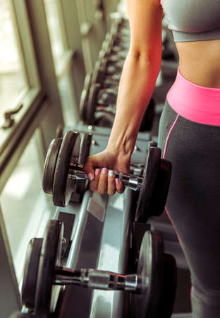 cropped out: Attractive young woman working out with dumbbells in gym, cropped Stock Photo