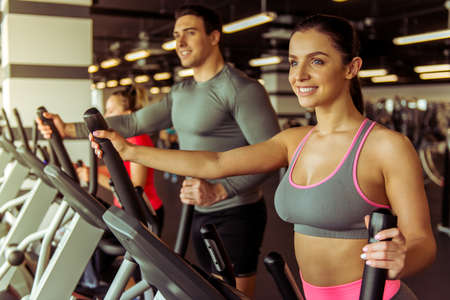 eliptica: Attractive young people working out on an elliptical trainer in gym and smiling Foto de archivo
