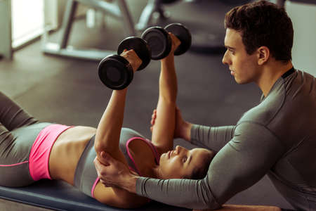 Attractive young woman working out with dumbbells in gym, handsome muscular trainer helping her