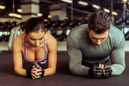laying abs exercise: Attractive young muscular man and woman doing plank exercise while working out in gym