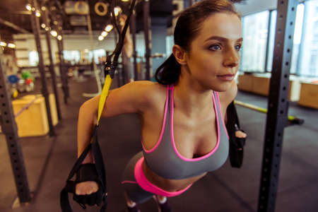Attractive young woman training with trx while working out in gym