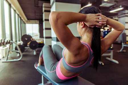 Back view of attractive young woman doing abs while working out in gym