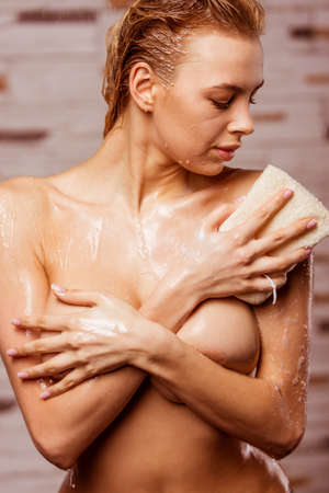 bare breast: Beautiful young naked woman enjoying pleasant shower, washing herself with a wisp of bast and covering her breast