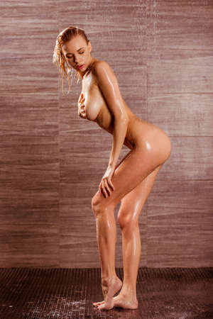 erotic breast: Passionate beautiful young naked woman taking shower, posing and covering her breast Stock Photo